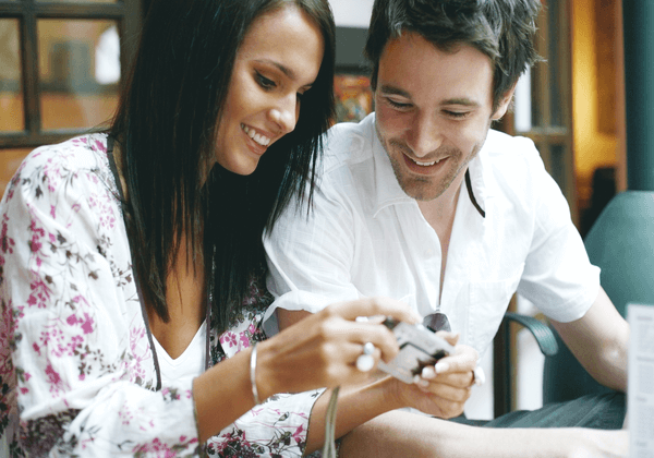 a woman showing her boyfriend images on her cell phone
