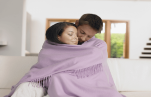 a woman and her boyfriend cuddling in a blanket